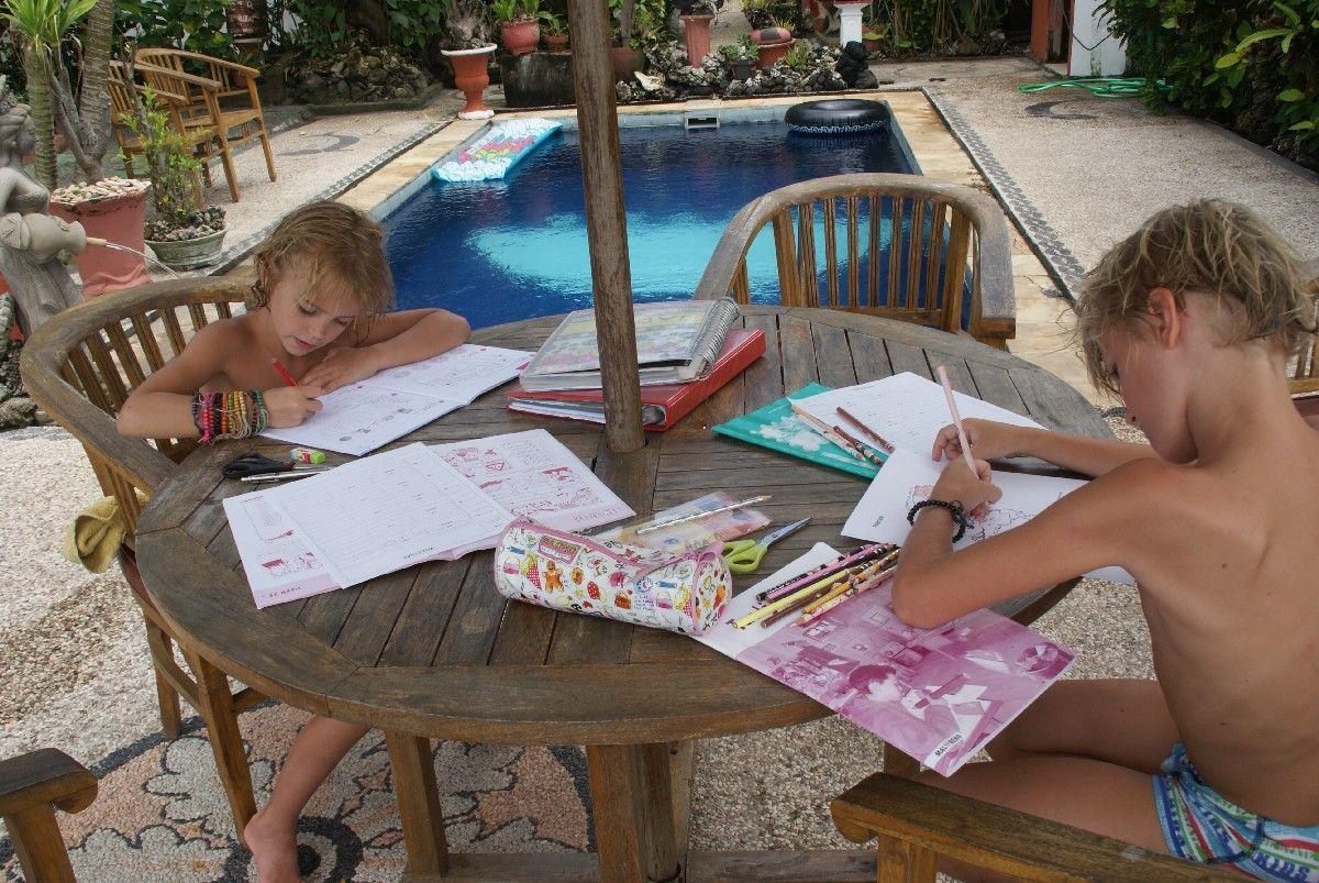 Huiswerk maken is geen straf. Als je klaar bent, mag je zwemmen.... Candidasa, Bali